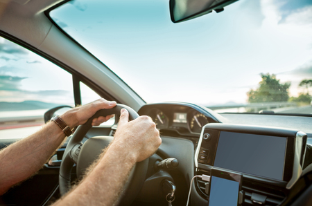 delegation: Mans (drivers) hands on steering wheel while driving a car - close up. Stock Photo