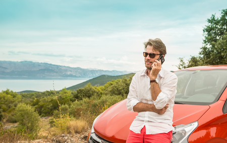 broken hill: Forty years old caucasian man (driver, tourist or businessman) talking on a mobile phone (smartphone) in front of a car. Landscape (mountain, sea) as background. Holiday (vacation) road trip concept.