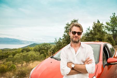 Gelukkig lachend veertig jaar oude blanke man (bestuurder, toeristische) ten overstaan van een auto. dag van de zomer en een prachtig landschap (bergen, zee) als achtergrond. Holiday (vakantie) road trip concept. Stockfoto