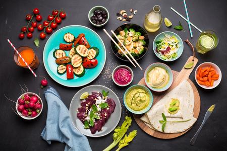Bunte vegetarische Festmahlzeit von oben. Gesunde Ernährung oder Lifestyle-Konzept. Flache Lagezusammensetzung (Draufsicht). Schwarze Tafel als Hintergrund.