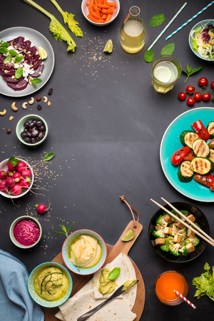 Colorful vegetarian feast dinner table from above (top view). Healthy diet or lifestyle concept. Flat lay composition with free text space. Black chalkboard as background.