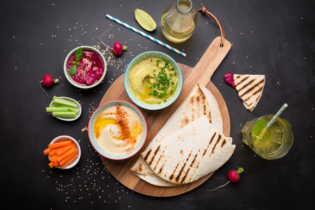 Colorful vegetarian snacks (appetizers) table. Various dips with pita bread. Black chalkboard as background. Flat lay composition from above (top view). Healthy diet or lifestyle concept.