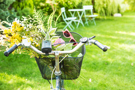Bicycle basket filled with romantic wild-flower bunch (bouquet) and pink sunglasses. Holiday (vacation, leisure) or countryside lifestyle concept. Sunny summer outdoor garden scenery as background.