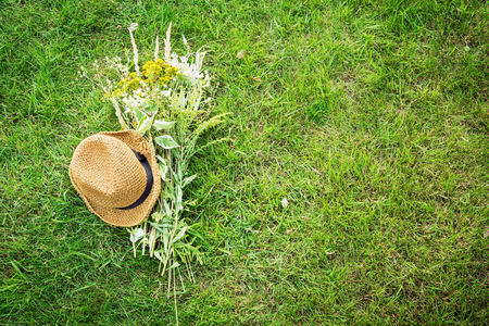 Straw hat and romantic wild-flower bunch (bouquet) on green grass lawn captured from above (top view). Background layout with free text space. Countryside lifestyle or summer relaxation concept.