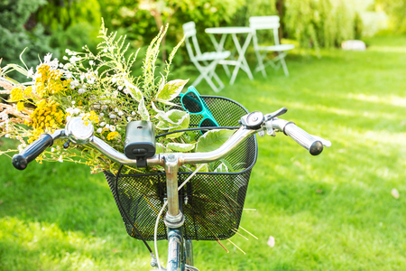 Bicycle basket filled with romantic wild-flower bunch (bouquet) and blue sunglasses. Holiday (vacation, leisure) or countryside lifestyle concept. Sunny summer outdoor garden scenery as background. 版權商用圖片