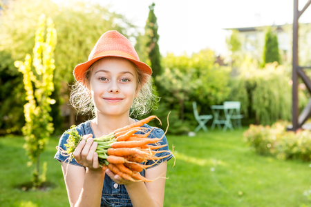 Happy smiling eight years old pretty blond caucasian child girl holding bunch of young carrots outdoor in the garden. Healthy lifestyle and gardening concept. Holiday - sunny summer day. 版權商用圖片