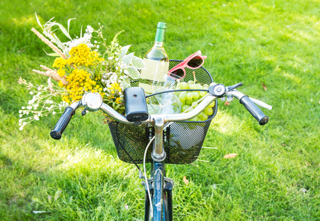 Summer outdoor romantic picnic in the garden. Bicycle basket filled with wild-flower bunch (bouquet), white wine, grapes and sunglasses. Holiday (vacation, leisure) or countryside lifestyle concept.