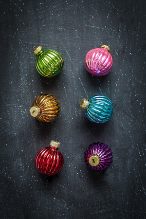 Colorful christmas balls on black chalkboard from above (top view). Simple modern flat lay composition with free text space.