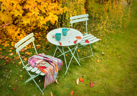 Colorful autumn garden nook - pastel green table, cups of hot tea, chairs and blanket. Outdoor fall relaxation scenery - countryside lifestyle concept. 版權商用圖片