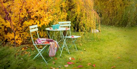 Colorato angolo giardino autunnale - tavolo verde pastello, tazze di tè caldo, sedie e coperta. Scenario di relax autunnale all'aperto - concetto di stile di vita di campagna.