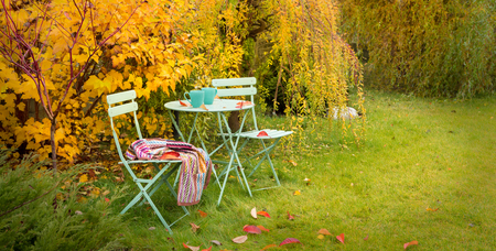 Colorful autumn garden nook - pastel green table, cups of hot tea, chairs and blanket. Outdoor fall relaxation scenery - countryside lifestyle concept.