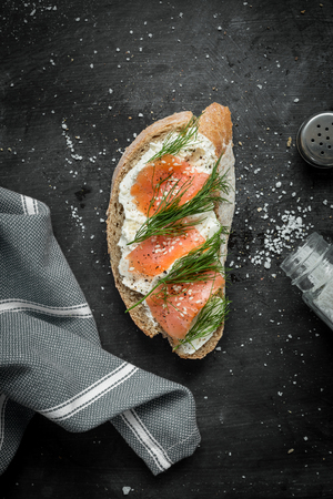 Salmon, cottage cheese and dill sandwich captured from above (top view). Black chalkboard as background. Flat lay composition with free text space.