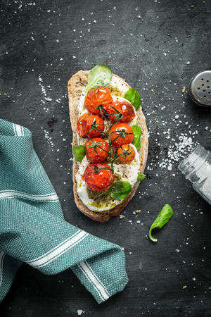 Italian mozzarella and roasted cherry tomatoes sandwich captured from above (top view). Black chalkboard as background. Flat lay composition with free text space. 版權商用圖片