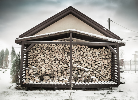 Winter - woodshed filled with stacked chopped birch firewood. Snowy scenery.