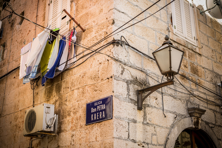 South Europe architecture charm. Historic sandstone building elevation with lantern, laundry, air conditioner and electrics. Croatia, Makarska old town street. 版權商用圖片