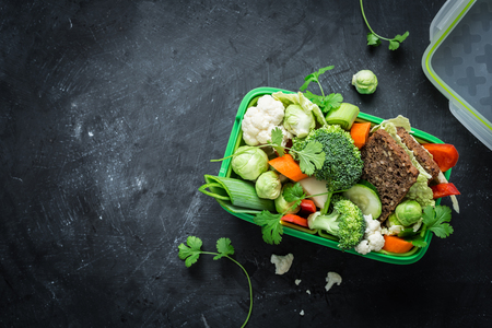 School lunch box with sandwich and various colorful vegetables on black chalkboard. Healthy eating habits concept. Flat lay composition (from above, top view). Background layout with free text space.