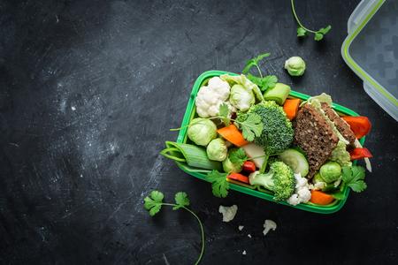 School lunch box met sandwich en diverse kleurrijke groenten op zwart bord. Gezonde eetgewoonten concept. Flat lay samenstelling (van boven, bovenaanzicht). Achtergrond lay-out met vrije tekst ruimte. Stockfoto
