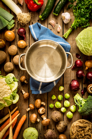 Cooking - empty pot with autumn (fall) vegetables around. Vintage rustic wood as background. Rural kitchen table - flat lay composition (from above, top view).