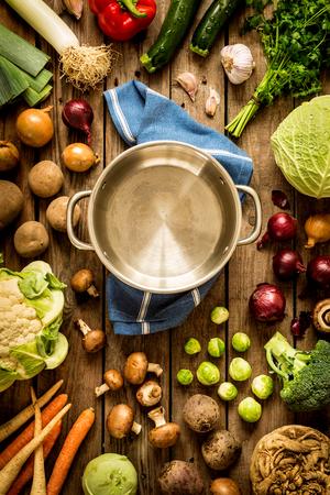 Koken - lege pot met herfst (herfst) groenten rond. Uitstekend rustiek hout als achtergrond. Landelijke keukentafel - vlakke lay-samenstelling (van bovenaf, bovenaanzicht). Stockfoto
