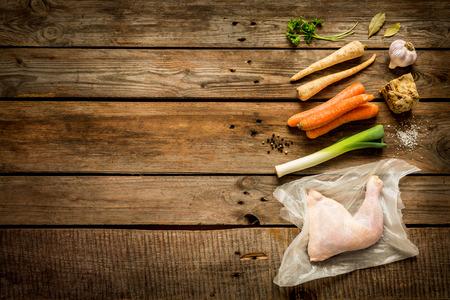 trompo de madera: Cocina - caldo de pollo (caldo, sopa) ingredientes de la receta en el fondo de madera rústica. Aves de corral y hortalizas de raíz - paisaje de la cocina desde arriba (vista desde arriba, en posición plana). Disposición con el espacio de texto libre.