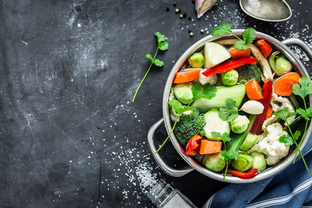 Various fresh vegetables in a pot - colorful fresh clear spring soup (vegetarian bouillon or stock). Kitchen scenery from above (top view). Black chalkboard background - layout with free text space.