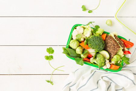 Green school or picnic lunch box with sandwich and various colorful vegetables. Healthy eating habits concept. Flat lay composition (top view) on white wood. Background layout with free text space.