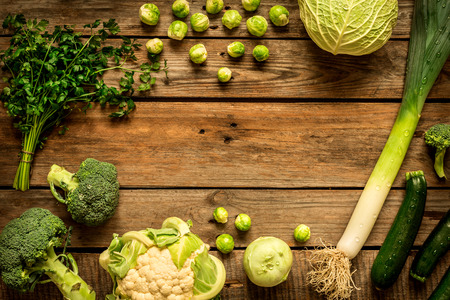 rustic kitchen: Green vegetables on vintage rustic wooden background. Rural kitchen table - flat lay composition (from above, top view). Layout with free text space. Stock Photo