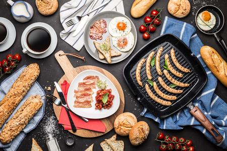 Volledig Engels ontbijt op zwarte bordachtergrond die hierboven wordt gevangen van (de hoogste vlakke mening, legt). Koffie, gebakken eieren, gebakken bonen, worstjes, broodjes, toast en spek.