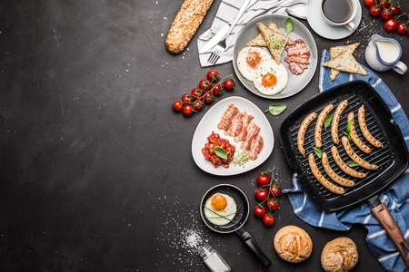Full english breakfast on black chalkboard background. Layout with free text (copy) space captured from above (top view, flat lay). Coffee, fried eggs, baked beans, sausages, bread rolls and bacon. 스톡 콘텐츠