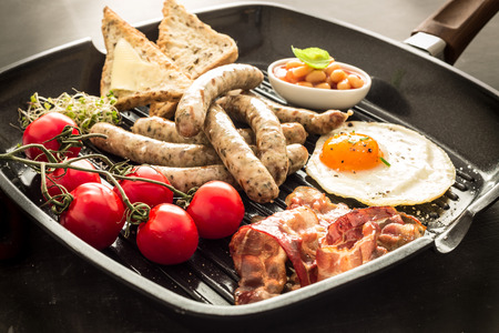 Full english breakfast on a grill pan. Fried egg, baked beans, sausages, toast, bacon and cherry tomatoes.