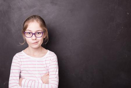 Portret van acht jaar oud, Kaukasisch, ongelukkig en ondeugend blond kindmeisje (jong geitje). Schoolbord (schoolbord) als achtergrond. Vrije tekst (kopie) ruimte. Onderwijs en jeugd concept.