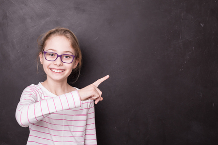 Eight years old, happy, smiling, caucasian blond child girl (kid) pointing at empty copy (text) space. School chalkboard (blackboard) as background. Education - carefree childhood concept. Фото со стока
