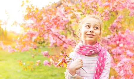 Eight years old, caucasian, happy smiling blond child girl (kid) admiring spring blooming garden. Pink flowering tree as background. Beauty of nature and carefree childhood concept.  Stock Photo