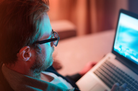 Adult caucasian man in glasses and casual clothes working by night on laptop computer - close up. Home, living room interior as background. Freelance worker or leisure (after hours) concept. Stock Photo