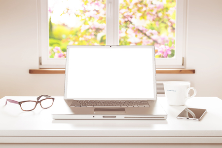 Laptop computer with blank screen on white table. Room with a window overlooking the blooming spring garden as background. Home - freelance job (remote work) office desk (workplace).