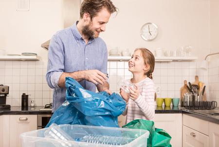 Recycling en ecologie - gelukkig Kaukasisch gezin (vader en dochter) sorteren (scheiden) huishoudelijk afval in de keuken. Lifestyle - ecologisch onderwijs en bewustwordingsconcept.