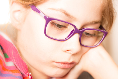 book concept: Face of eight years old, caucasian, blond and thoughtful child girl (kid) in glasses while reading a book. Close up portrait (macro). Childhood and education concept. Stock Photo