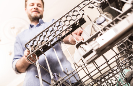 Forty years old caucasian man using (loading) dishwasher machine in the home kitchen - household chores.  Reklamní fotografie