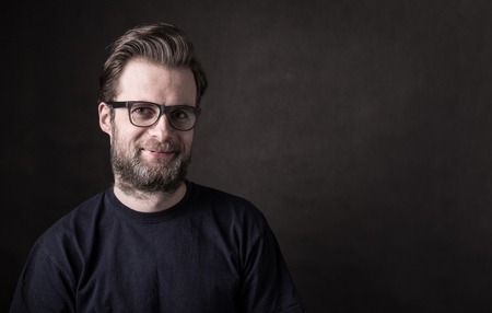 Portrait of happy smiling forty years old caucasian man in casual t-shirt and glasses. Black background, dark moody concept. Layout with free text (copy) space.
