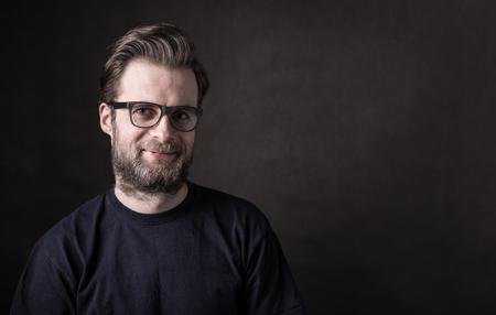 Retrato de feliz sonriente hombre caucásico cuarenta años en camiseta y gafas casual. fondo negro, el concepto de mal humor oscuro. Diseño con el texto en el espacio libre (copia). Foto de archivo - 75784655