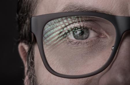 Oog en glazen - Kaukasische man gezicht close-up (macro). Zwarte achtergrond, donker humeurig licht. Stockfoto