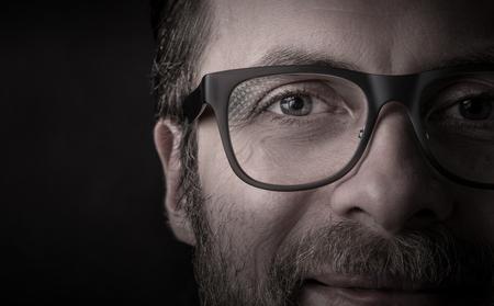 Ogen en glazen - gelukkig glimlachend gebaard Kaukasisch man gezicht dicht omhoog (macro). Succesvol zakenmanportret op zwarte achtergrond, donker humeurig licht. Lay-out met vrije tekst (kopie) ruimte. Stockfoto