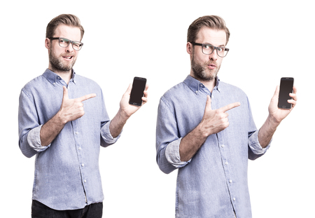 Forty years old caucasian handsome man in blue shirt and glasses pulling faces while pointing at (presenting) mobile phone (smartphone) - isolated on white background.