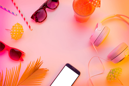 Summer holiday (vacation) relaxation concept. Mobile phone (smartphone), headphones, sunglasses and fruity drink from above (top view, flat lay). Colorful background with free text (copy) space. Stock Photo