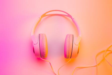 Hoofdtelefoons op kleurrijke (veelkleurige toonovergangen) achtergrond. Posterindeling met vrije tekst (kopie) ruimte.