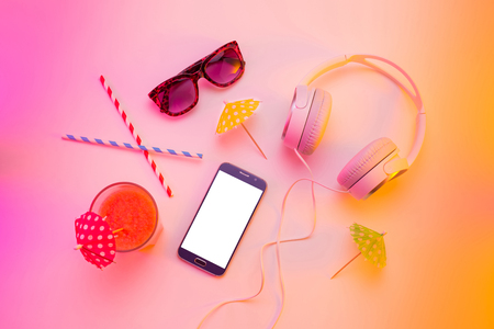 Summer holiday (vacation) relaxation concept. Mobile phone (smartphone), headphones, sunglasses and fruity drink from above (top view, flat lay). Colorful (multicolor tonal transitions) background.