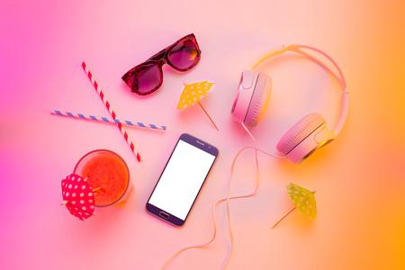 Zomervakantie (vakantie) ontspanning concept. Mobiele telefoon (smartphone), hoofdtelefoon, zonnebril en fruitige drank van bovenaf (bovenaanzicht, vlak leggen). Kleurrijke (veelkleurige toonovergangen) achtergrond. Stockfoto