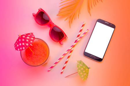 Summer holiday (vacation) relaxation concept. Mobile phone (smartphone), sunglasses and fruity drink from above (top view, flat lay). Colorful (multicolor tonal transitions) background.