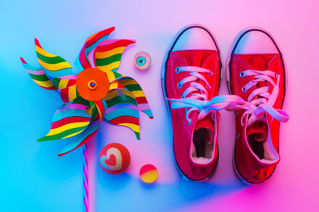 Sneakers and toys (pinwheel and rubber balls) captured from above (top view, flat lay). Colorful (multicolor tonal transitions) background. Childhood concept. Stock Photo