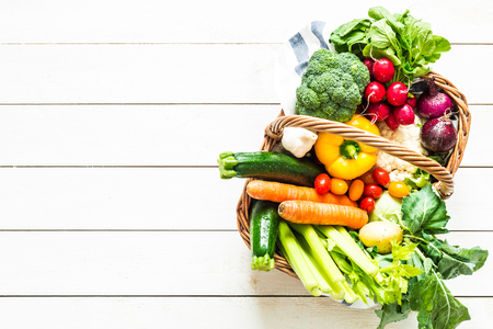 Colorful organic spring vegetables in wicker basket - captured from above (top view). White rustic wooden table as background. Layout with free text (copy) space. Fresh harvest from the garden.